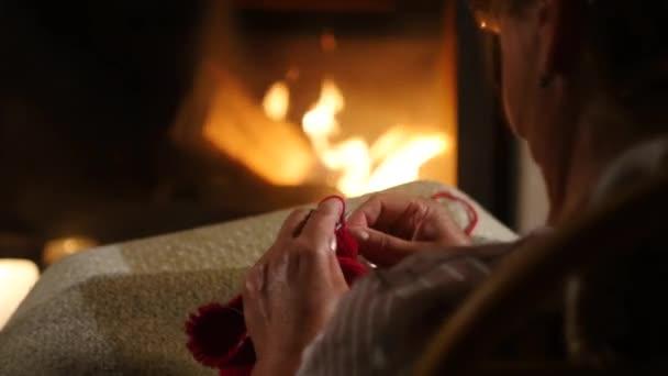 Nagymama kötögetni egy pulóvert egy kandalló előtt ülő