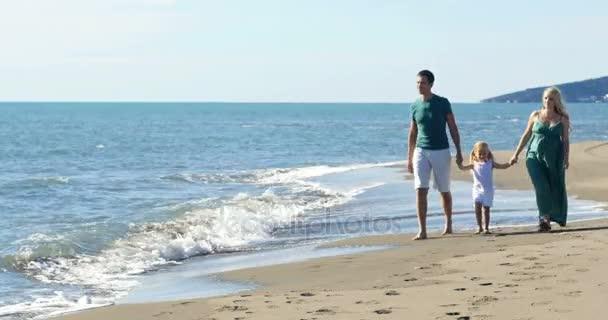 Máma táta a dcera chodí po pláži