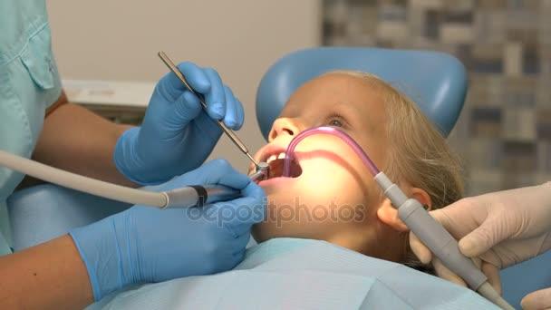 Kleines Mädchen sitzt in der Zahnarztpraxis