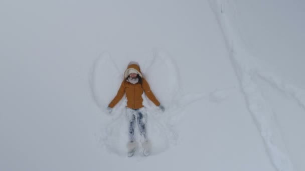 Young woman making snow angels