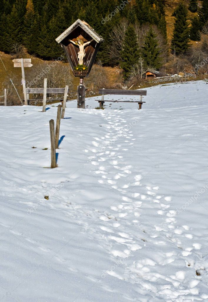 path in the snow leads to the small shrine of Christ