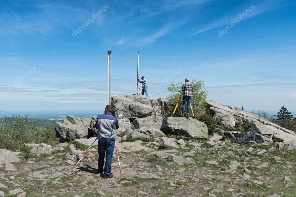 The surveyor measures the top of the mountain