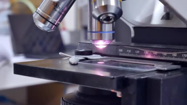 Close up hand scientist using light microscope in laboratory.