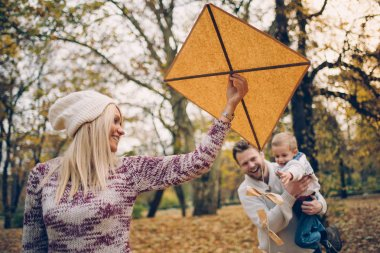 Happy Caucasian parents and his son enjoying flying toy kite in nature