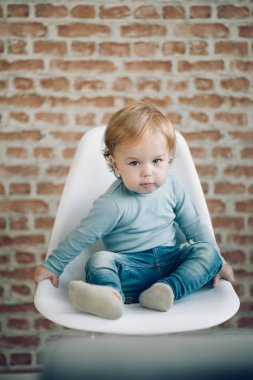 Toddler sitting in chair.
