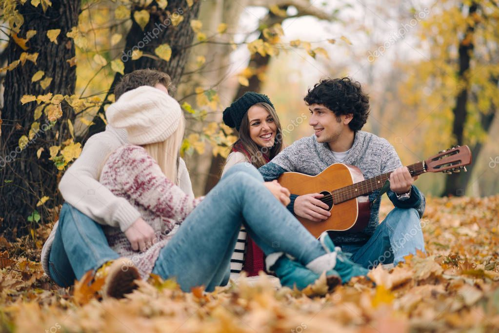 Friends playing guitar outdoor