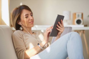 Young beautiful woman sitting on sofa and using tablet for coumunication.