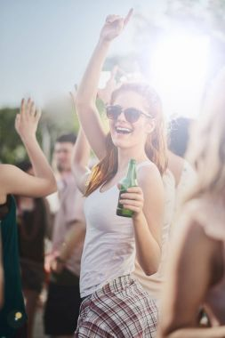 Ginger girl dancing, drinking an having a good time at outdoor party