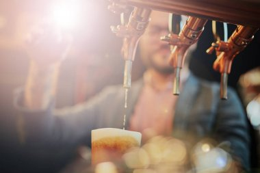 Tattooed caucasian barman pouring beer while standing in pub. Selective focus on glass. stock vector