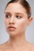 Gyönyörű nő pózol anti-age krém az arcon.