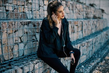 Young attractive brunette resting after running while putting earphones to listen music.