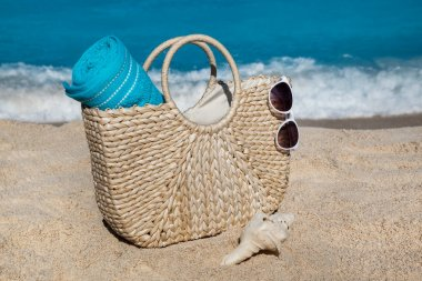 Straw bag with blue towel and sunglasses on tropical sand beach