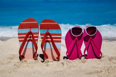 Tropical beach in the summer with flip flops in the sand and sun