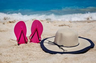 Tropical beach in the summer with flip flops and hat