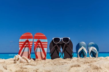 Set of family sandals on the sandy beach, vacation concept