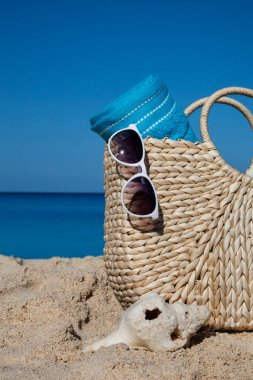 Closeup of summer straw bag with blue towel and sunglasses on a