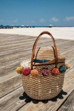 Summer straw bag on wooden bridge at the beach