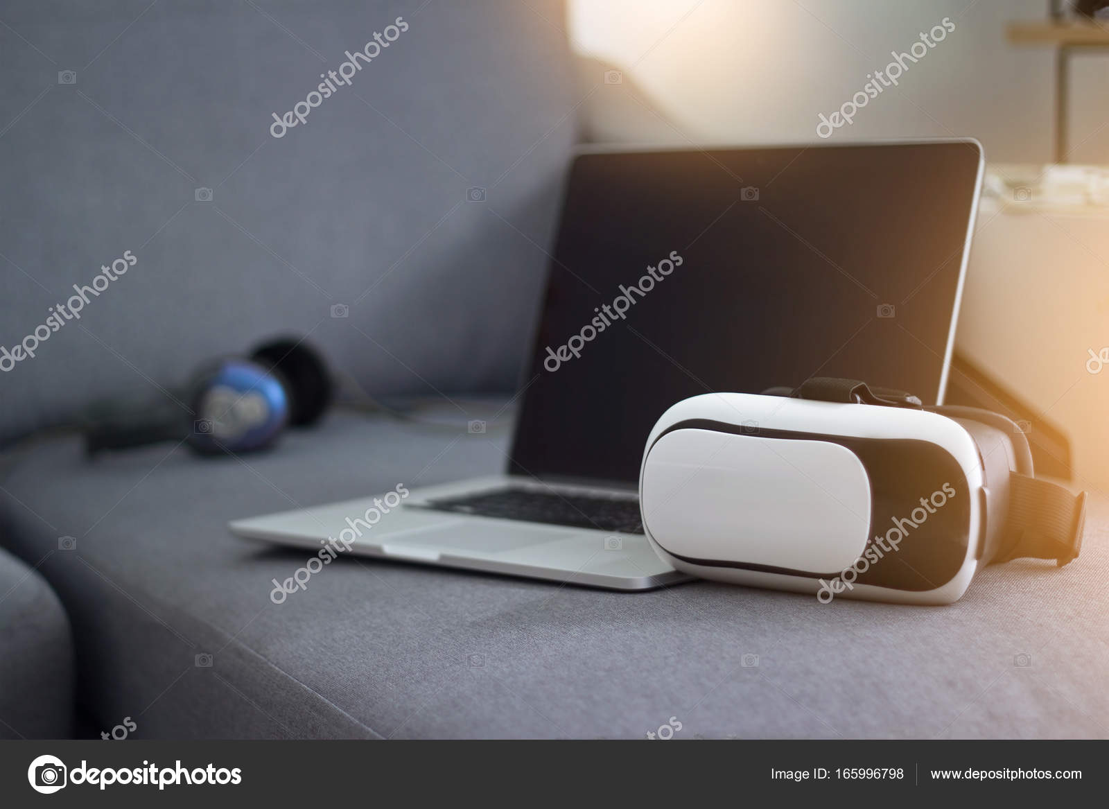 171014dbe521 VR headset with headphone and laptop on sofa in living room — Stock Photo