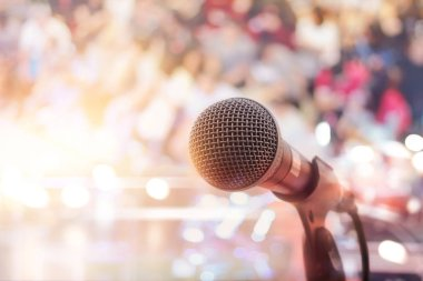 Microphone on concert stage with people background