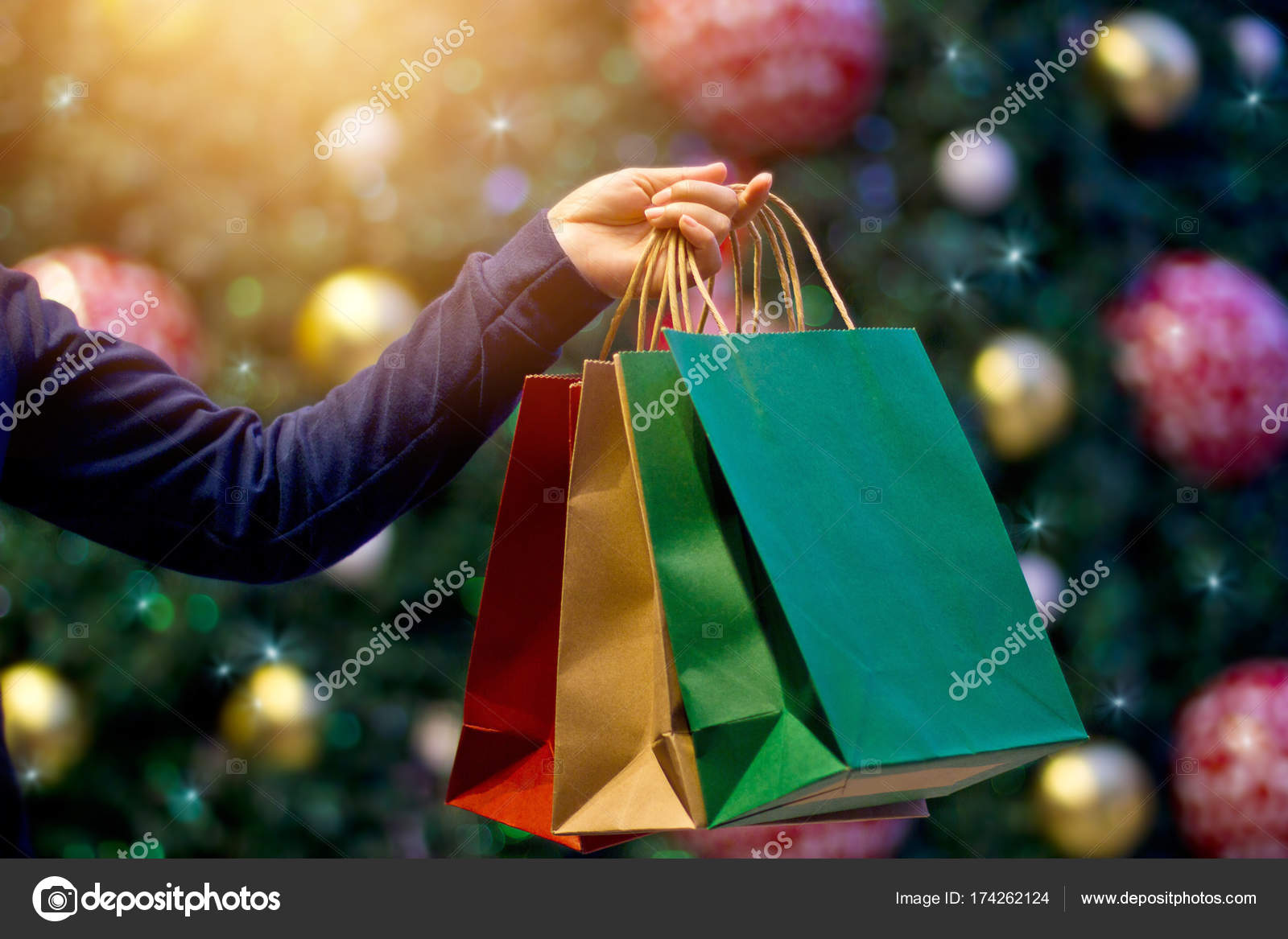 Christmas shopping bags in hand on christmas decoration u stock