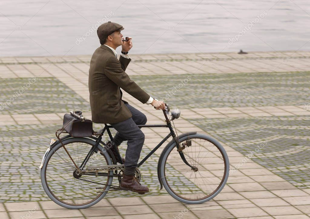STOCKHOLM - SEPT 23, 2017: Elegant man smoking a pipe riding a retro bicycle, dressed in old fashioned tweed clothes in the Bike in Tweed event September 23, 2017 in Stockholm, Sweden