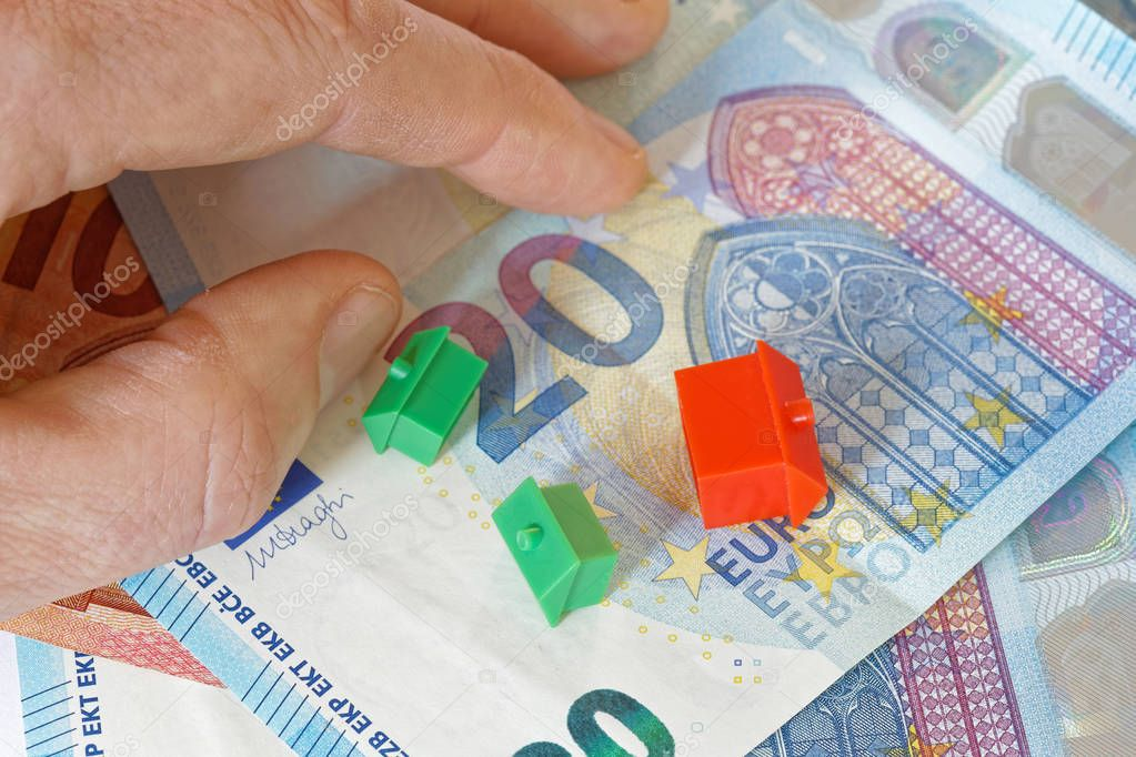 Overturned miniature houses and a hand on top of European Euro currency symbolising expensive houses and flats