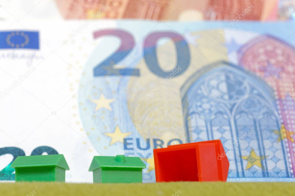 Overturned miniature houses in front of European Euro currency symbolising expensive houses and flats