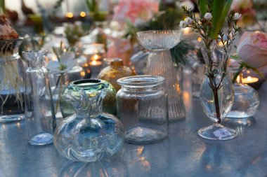 Many glass vase in different shapes with flowers on a table