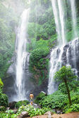 Man standing near beautiful waterfall