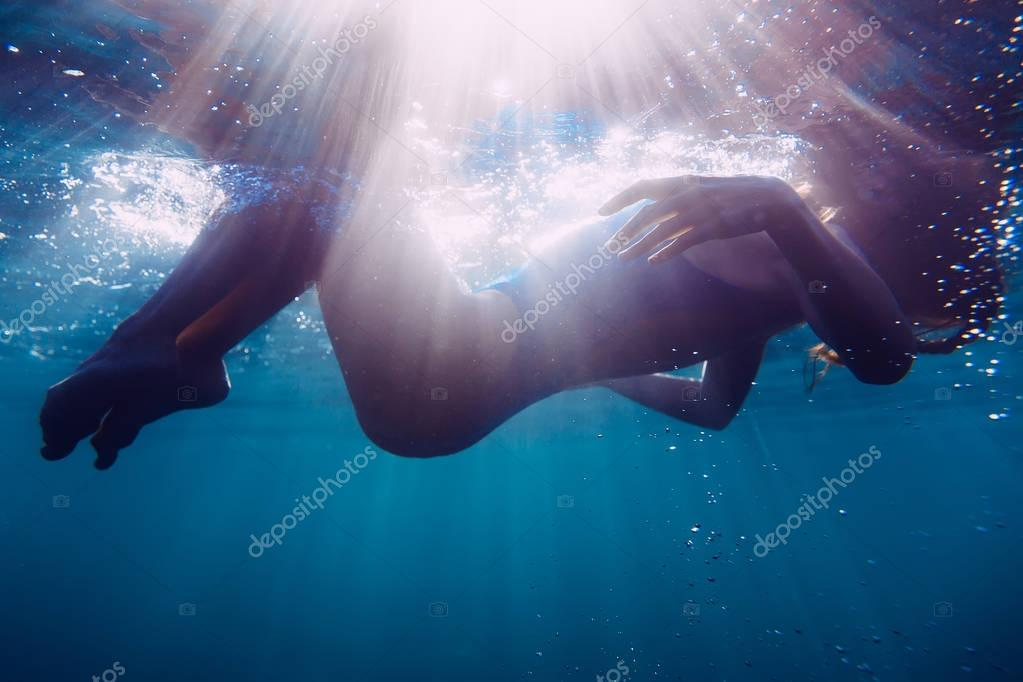 Beautiful young woman is underwater.