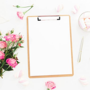 Beauty composition with marshmallow,  pink roses bouquet and clipboard on white background. Top view. Flat lay. Beauty blog, copy space