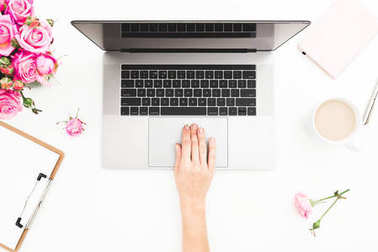 Girl working on laptop. Woman workspace with female hands, laptop, pink roses bouquet, coffee mug, diary on white table. Top view. Flat lay.