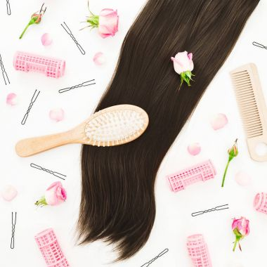 Frame with combs for hair styling, pink roses and hairpins on white background. Beauty blog composition. Flat lay, top view