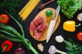 Fényképek Az élelmiszer-összetétel nyers hússal, a főzés fórumon, kés, Libaleves a sötét tábla. Felülnézet. Lapos feküdt