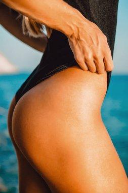 Beautiful young girl relaxing  on a beach of  tropical ocean, wearing stylish bikini