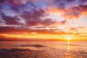 Fotografia Brillante tramonto o allalba nelloceano. Paesaggio con tramonto caldo o alba colori