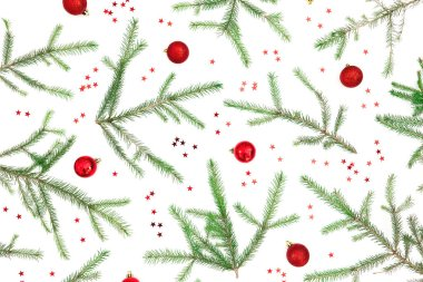 Christmas pattern of fir tree branches and red decoration on whi