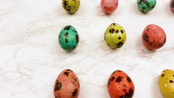 Fürj színes húsvéti tojást a márvány felületre. Közelről.