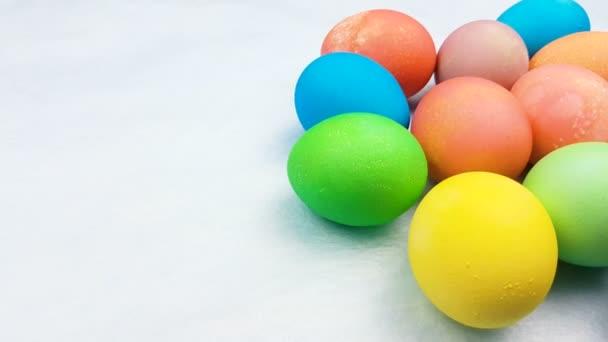 Barevné velikonoční vejce na pastelově modré pozadí. Detailní záběr