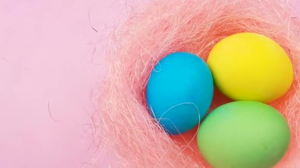 Színes húsvéti tojást a szép fészket pasztell rózsaszín háttér.