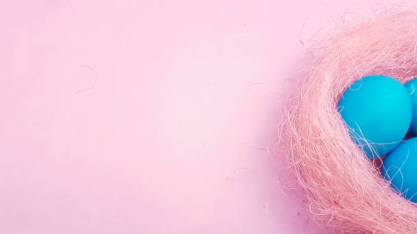76efdc27e93009 Pisanki w ładne gniazdo na pastelowy różowy tło kolor.– filmik stockowy