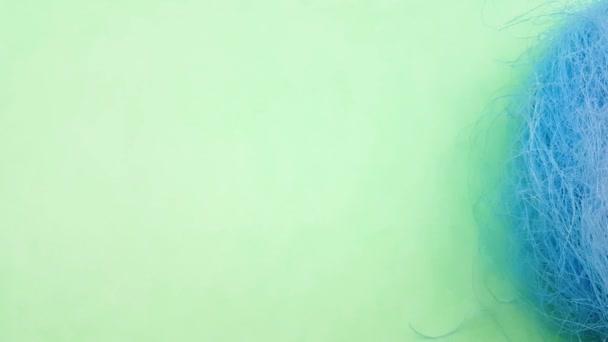 Színes Húsvét ikra-ban kék pasztell fészek zöld háttér. Közelről.