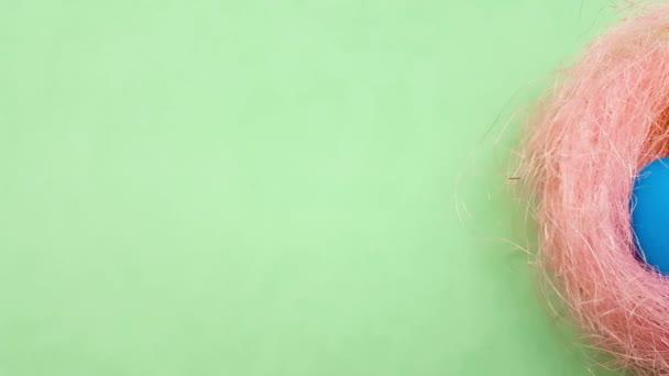 Farbe Ostereier in rosa Pastell Nest auf grünem Hintergrund. Nahaufnahme.