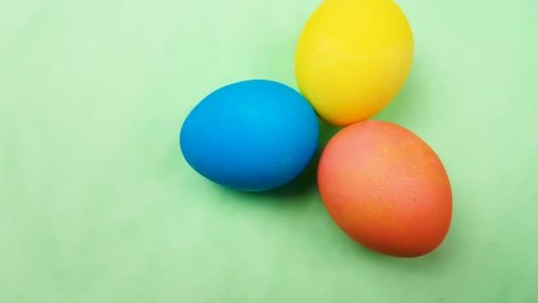 Barevná velikonoční vajíčka na pastelově zeleném pozadí. Detailní záběr