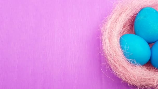 Color easter eggs in pastel pink nest on purple background.