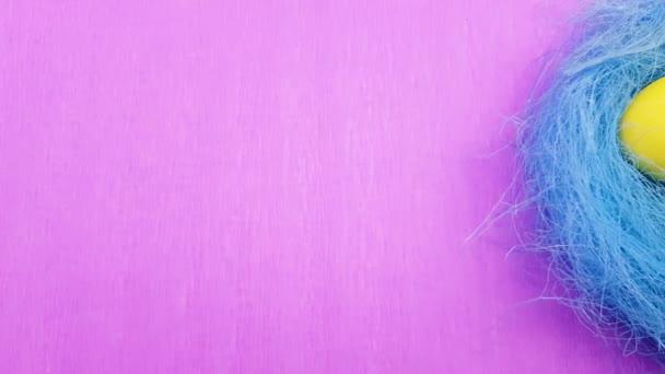 Színes Húsvét ikra-ban kék pasztell fészek, lila háttér. Közelről.