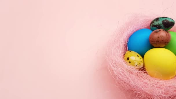 Easter color quail and chiken eggs in pink nest on pastel background.