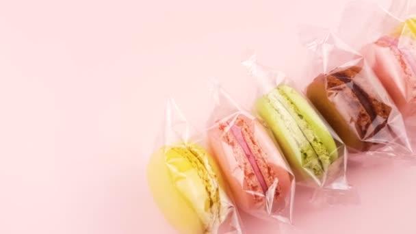 Barevné sladké makronky nebo macaron do průhledného obalu na pastelově růžové pozadí