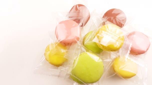 Barevné sladké makronky nebo macaron průhledného obalu bílé pozadí