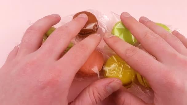 Ruce dejte barevné sladké makronky nebo macaron do průhledného obalu na pastelově růžová